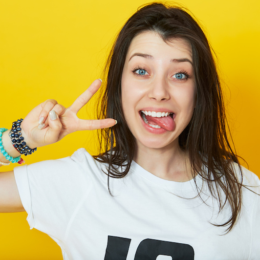 Girl showing her tongue and peace gesture